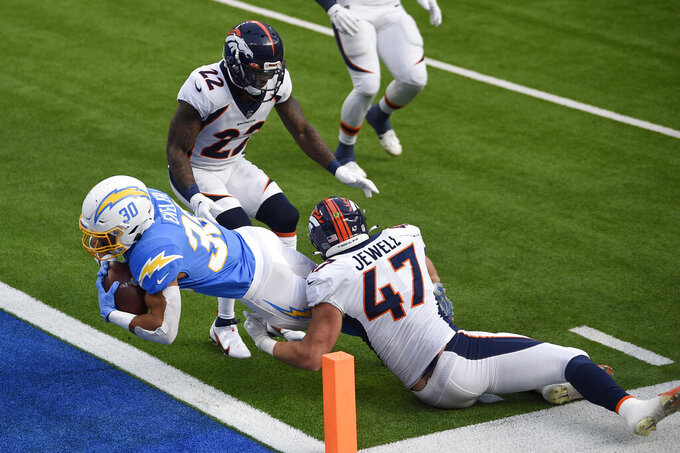 Los Angeles Chargers running back Austin Ekeler (30) scores a touchdown past Denver Broncos inside linebacker Josey Jewell (47) and strong safety Kareem Jackson (22) during the first half of an NFL football game Sunday, Dec. 27, 2020, in Inglewood, Calif. (AP Photo/Kelvin Kuo)