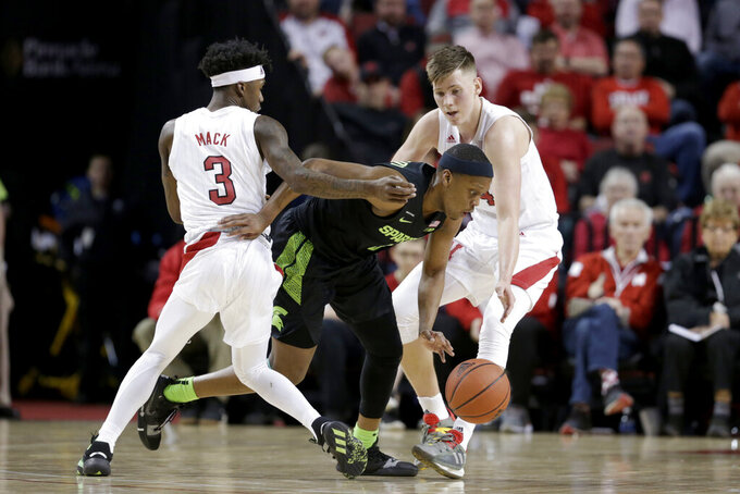 Michigan State's Cassius Winston, center, drives between Nebraska's Cam Mack (3) and Nebraska guard Thorir Thorbjarnarson (34) during the first half of an NCAA college basketball game in Lincoln, Neb., Thursday, Feb. 20, 2020. (AP Photo/Nati Harnik)