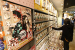 "Copies of the final and 23rd volume of the ""Demon Slayer"" manga series are lined up on bookshelves at a store in Tokyo on Dec. 4, 2020. ""Demon Slayer: Kimetsu no Yaiba the Movie: Mugen Train,"" directed by Haruo Sotozaki, has become the biggest grossing film for Japan, including live-action films, and has struck a chord with pandemic-era Japan, and possibly with the world. (Kyodo News via AP)"