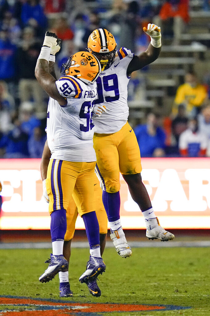 LSU defensive lineman Jaquelin Roy, right, celebrates his sack of Florida quarterback Kyle Trask with defensive end Neil Farrell Jr. (92) during the first half of an NCAA college football game Saturday, Dec. 12, 2020, in Gainesville, Fla. (AP Photo/John Raoux)