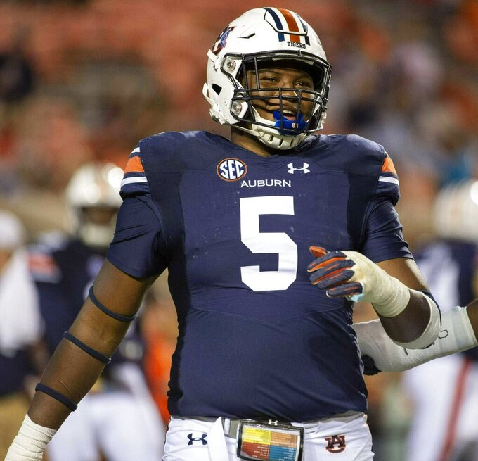 FILE - In this Sept. 29, 2018, file photo, Auburn defensive lineman Derrick Brown (5) warms up after a lightning delay in the first half of an NCAA college football game against Southern Mississippi, in Auburn, Ala. The SEC, a conference that prides itself on producing great defensive linemen and linebackers, must find candidates to replace all the guys heading into the pros. Alabama's Raekwon Davis and Auburn's Derrick Brown both enter the summer as legitimate All-America candidates as they attempt to lead their teams.(AP Photo/Vasha Hunt, File)
