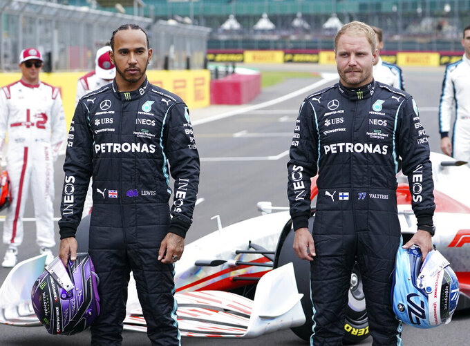 """Mercedes driver Lewis Hamilton of Britain, left, and Mercedes driver Valtteri Bottas of Finland pose with a model of the 2022 F1 car revealed in """"F1 One Begins"""" event at the Silverstone circuit, Silverstone, England, Thursday, July 15, 2021. F1 will introduce a new rules and new regulations in 2022. (AP Photo/Jon Super)"""