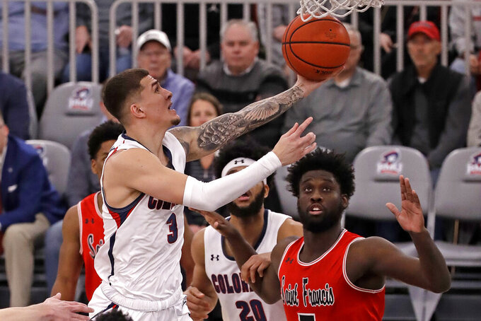 Robert Morris' Dante Treacy (3) takes a shot in front of St. Francis'sMyles Thompson, right, during the first half of an NCAA college basketball game for the Northeastern Conference men's tournament in Pittsburgh, Tuesday, March 10, 2020. (AP Photo/Gene J. Puskar)