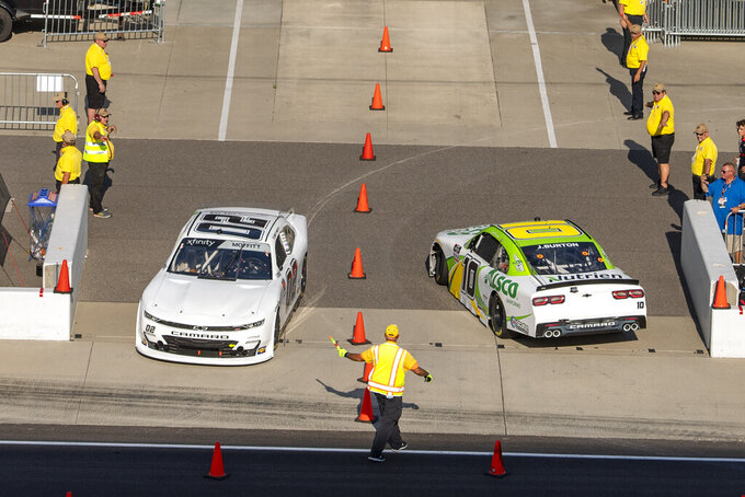 Brett Moffitt (02), left, leaves Gasoline Alley while Jeb Burton (10) heads in during practice for the NASCAR Xfinity Series auto race at Indianapolis Motor Speedway, Friday, Aug. 13, 2021, in Indianapolis. (AP Photo/Doug McSchooler)