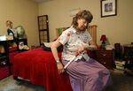 In this Aug. 22, 2018 photo, April Box uses a roller to work on her hip muscles at her home in Spokane, Wash.  Millions of people covered under the Affordable Care Act will see only modest premium increases next year, and some will get a price cut. That's the conclusion from an exclusive analysis of the besieged but resilient program that still divides voters heading into this year's midterm elections.  (AP Photo/Ted S. Warren)