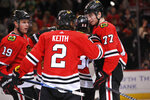 Chicago Blackhawks' Duncan Keith (2) celebrates with teammates Kirby Dach (77) and Jonathan Toews (19) after scoring a goal during the second period of an NHL hockey game against the San Jose Sharks Wednesday, March 11, 2020, in Chicago. (AP Photo/Paul Beaty)