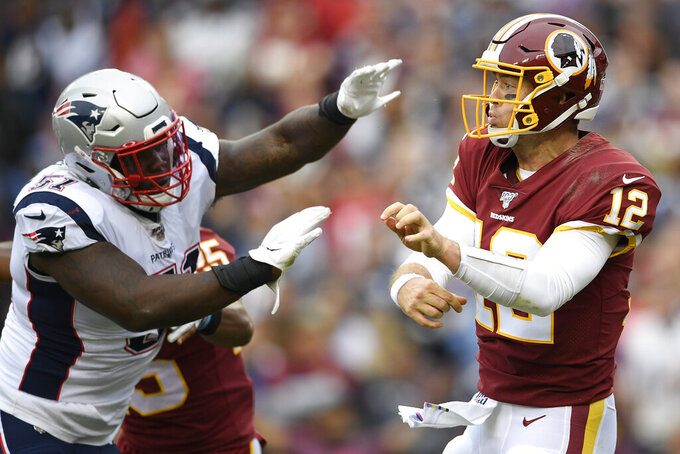 Washington Redskins quarterback Colt McCoy (12) works under pressure from New England Patriots linebacker Ja'Whaun Bentley (51) during the second half of an NFL football game, Sunday, Oct. 6, 2019, in Washington. (AP Photo/Nick Wass)