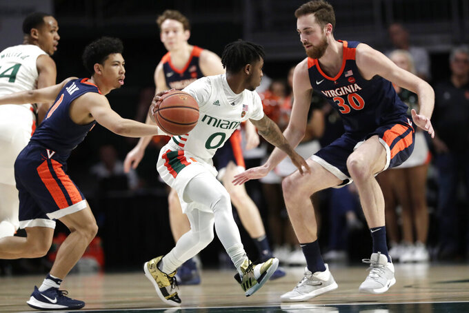 Miami guard Chris Lykes (0) controls the ball as Virginia guard Kihei Clark, left, and forward Jay Huff (30) defend during the first half of an NCAA college basketball game, Wednesday, March 4, 2020, in Coral Gables, Fla. (AP Photo/Lynne Sladky)