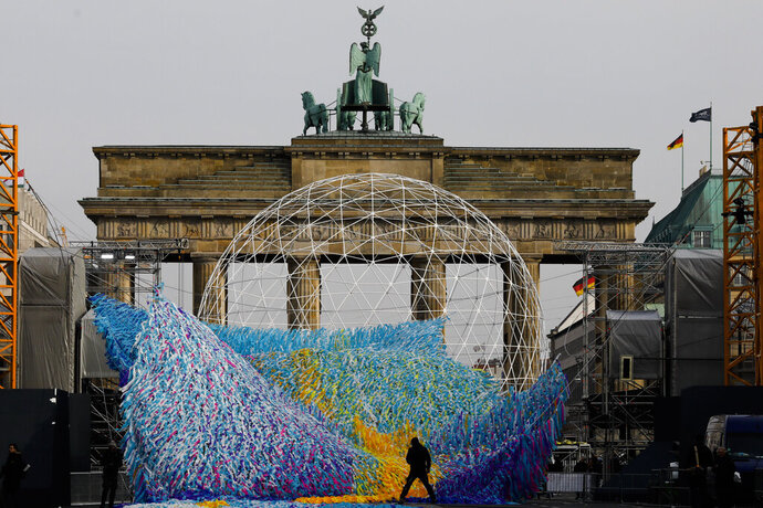 The skynet artwork 'Visions In Motion' is set to overhang the 'Strasse des 17. Juni' (Street of June 17) boulevard in front of the Brandenburg Gate in Berlin, Germany, Friday, Nov. 1, 2019. The art work by Patrick Shearn was made with about 100.000 streamers with written messages and is part of the celebrations marking the 30th anniversary of the fall of the Berlin Wall on Nov 9, 2019. (AP Photo/Markus Schreiber)