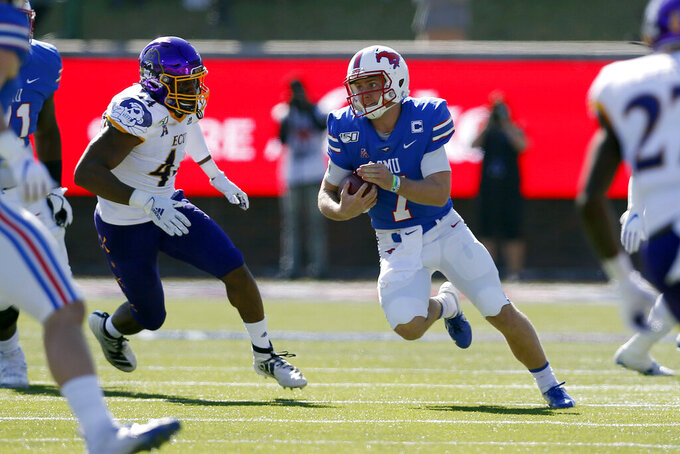 SMU quarterback Shane Buechele (7) looks for room to run while East Carolina cornerback Malik Fleming (4) gives chase during the first half of an NCAA college football game, Saturday, Nov. 9, 2019, in Dallas. (AP Photo/Roger Steinman)