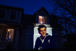 An image of veteran Stephen Kulig is projected onto the home of his daughter, Elizabeth DeForest, as she looks out the window of a spare bedroom as her husband, Kevin, sits downstairs in Chicopee, Mass., Sunday, May 3, 2020. Kulig, a U.S. Navy veteran and resident of the Soldier's Home in Holyoke, Mass., died from the COVID-19 virus at the age of 92. After saying goodbye to her father for the last time in person, Elizabeth slept in the spare bedroom upstairs for two weeks as a precaution against possibly infecting her husband. Seeking to capture moments of private mourning at a time of global isolation, the photographer used a projector to cast large images of veterans on to the homes as their loved ones are struggling to honor them during a lockdown that has sidelined many funeral traditions. (AP Photo/David Goldman)