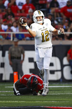 Florida International's Max Bortenschlager (12) throws away the ball while being tackled by Texas Tech's Brandon Bouyer-Randle (2) during the first half of an NCAA college football game on Saturday, Sept. 18, 2021, in Lubbock, Texas. (AP Photo/Brad Tollefson)