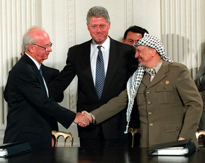 FILE - President Bill Clinton, center, looks on as Israeli Prime Minister Yitzhak Rabin, left, and PLO leader Yasser Arafat shake hands in the East Room of the White House after signing the Mideast accord in Washington on Sept. 28, 1995. A new documentary