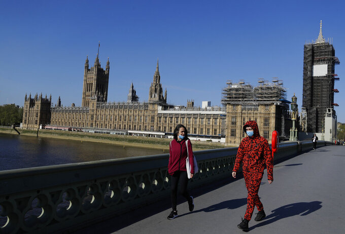 People wear masks as they walk near Britain's Houses of Parliament as the country is in lockdown to help curb the spread of coronavirus, in London, Tuesday, April 21, 2020. Britain's Parliament is going back to work, and the political authorities have a message for lawmakers: Stay away. U.K. legislators and most parliamentary staff were sent home in late March as part of a nationwide lockdown to slow the spread of the new coronavirus. With more than 16,500 people dead and criticism growing of the government's response to the pandemic, legislators are returning Tuesday — at least virtually — to grapple with the crisis.(AP Photo/Kirsty Wigglesworth)