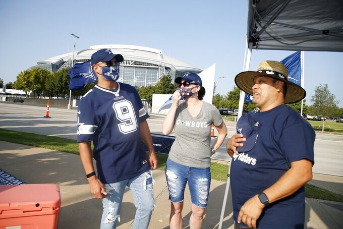 Dallas Cowboys fans, talk with Gilbert Montez, right, of Los Angeles, as they tailgate outside of AT&T Stadium before an NFL football game agains the Atlanta Falcons in Arlington, Texas, Sunday, Sept. 20, 2020. (AP Photo/Michael Ainsworth)
