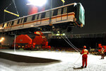 Workers load an exported subway train cartridge to a container ship at a dockyard in Qingdao in east China's Shandong province on Sept. 25, 2020. China has passed a new law restricting sensitive exports to protect national security, allowing Beijing to reciprocate against the U.S. as tensions mount between the sides over trade and technology. (Chinatopix via AP)