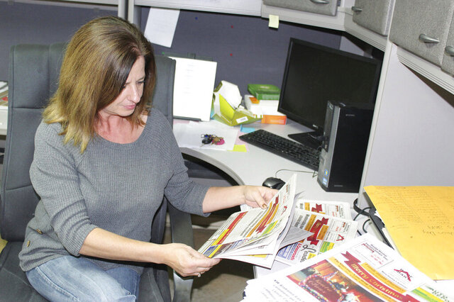 This Jan. 10, 2020 photo,  Stephanie Minor looks through copies of the latest edition of the weekly Lamar Leader in Sulligent, Ala.  Minor, who started working at the paper in 1998 as a typesetter, became the newspaper's owner on Dec. 20. (Zack Plair/The Commercial Dispatch via AP)