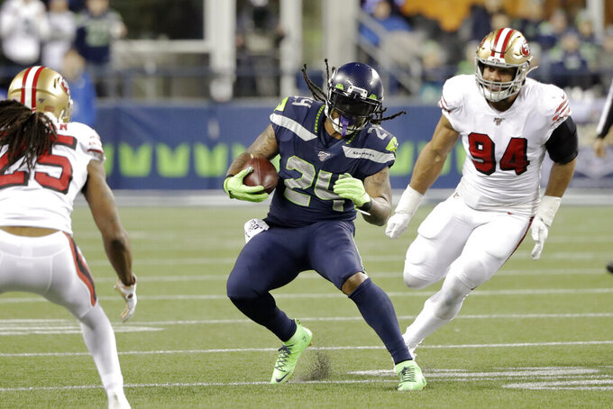 Seattle Seahawks' Marshawn Lynch (24) carries between San Francisco 49ers' Richard Sherman (25) and Solomon Thomas (94) during the second half of an NFL football game, Sunday, Dec. 29, 2019, in Seattle. (AP Photo/Ted S. Warren)