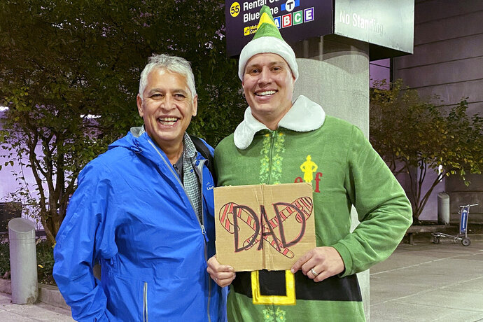 Doug Henning, right, who was adopted as a baby, poses with his biological father after meeting face to face for the first time on Tuesday, Nov. 24, 2020, at Logan International Airport in Boston. Henning, of Eliot, Maine, wore a costume like the one actor Will Ferrell's character wore in the movie