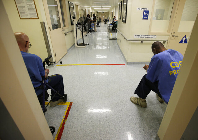 FILE — In this June 20, 2018, file photo, a pair of inmates wait for medical treatment at the California Medical Facility in Vacaville, Calif. Attorneys representing California inmates are urging state officials and a federal judge to advance one of every 10 prisoners to the front of the line for coronavirus vaccinations, saying it would help ease the burden on hospitals while helping control outbreaks inside state lockups. (AP Photo/Rich Pedroncelli, File)