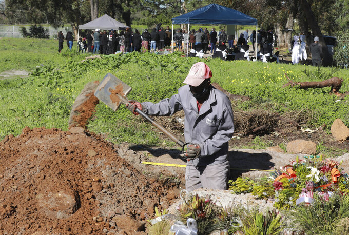 A gravedigger works in the COVID-19 section of the Maitland Cemetary in Cape Town, South Africa, Wednesday, July 15, 2020 as a burial takes place in the background. South Africa has surpassed the UK in its number of confirmed coronavirus cases and now has the world's eighth-highest number of confirmed cases at 298,292, which is nearly half of all the confirmed cases on the African continent. (AP Photo/Nardus Engelbrecht)