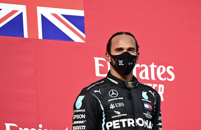 Mercedes driver Lewis Hamilton of Britain stands on the podium after winning the Emilia Romagna Formula One Grand Prix, at the Enzo and Dino Ferrari racetrack, in Imola, Italy, Sunday, Nov.1, 2020. (Miguel Medina, Pool via AP)