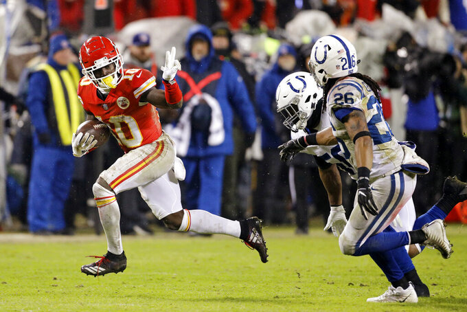 FILE - In this Jan. 12, 2019, file photo, Kansas City Chiefs wide receiver Tyreek Hill (10) gives Indianapolis Colts linebacker Anthony Walker (50) and safety Clayton Geathers (26) the peace sign as he rushes for a first down during an NFL AFC Divisional football game at Arrowhead Stadium in Kansas City, Mo. The Kansas City Chiefs have made a habit of inciting controversy during the NFL draft in the Andy Reid era by acquiring players that have a history of off-the-field issues. The team took a chance on cornerback Marcus Peters, who was traded away after getting into trouble with coaches. It drafted running back Kareem Hunt, then quickly cut him when he kicked a woman in a hotel hallway. And it picked wide receiver Tyreek Hill, who is currently dealing with a domestic violence case that centers on the 3-year-old child he shares with his fiance. (AP Photo/Colin E. Braley, File)