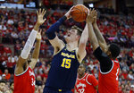 Michigan center Jon Teske, center, goes up for a shot between Ohio State forward Kaleb Wesson, left, and guard Luther Muhammad during the first half of an NCAA college basketball game in Columbus, Ohio, Sunday, March 1, 2020. (AP Photo/Paul Vernon)