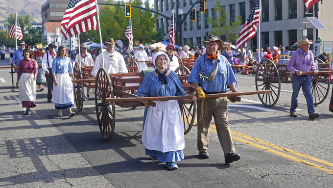 People pull handcarts during the Pioneer Day Parade, Friday, July 23, 2021, in Salt Lake City. People in Utah are gathering to celebrate the state's history and recognize early Mormon pioneers who trekked West in search of religious freedom. Pioneer Day is a beloved only-in-Utah holiday every July 24 that features parades, rodeos, fireworks and more. The festivities were canceled last year because of the pandemic.(AP Photo/Rick Bowmer)