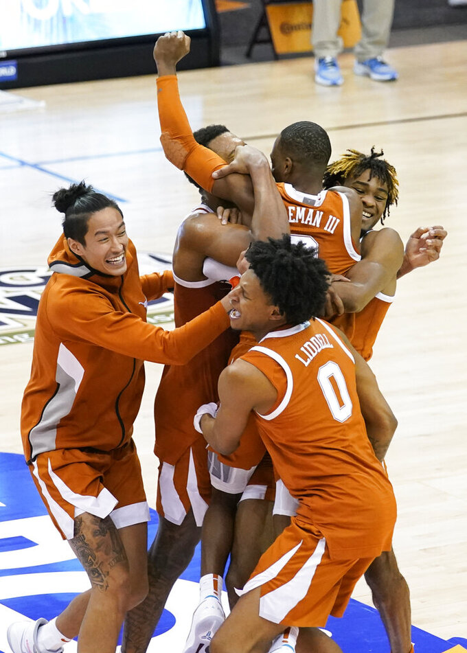 Texas guard Matt Coleman III (2) is hugged by teammates after Texas beat North Carolina 69-67 to win the NCAA college basketball game for the championship of the Maui Invitational, Wednesday, Dec. 2, 2020, in Asheville, N.C. Coleman was the MVP with the winning basket and high score of 22 points. (AP Photo/Kathy Kmonicek)