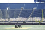 Referees break their meeting before the first half of an NCAA college football game between Michigan and Michigan State, Saturday, Oct. 31, 2020, in Ann Arbor, Mich. (AP Photo/Carlos Osorio)
