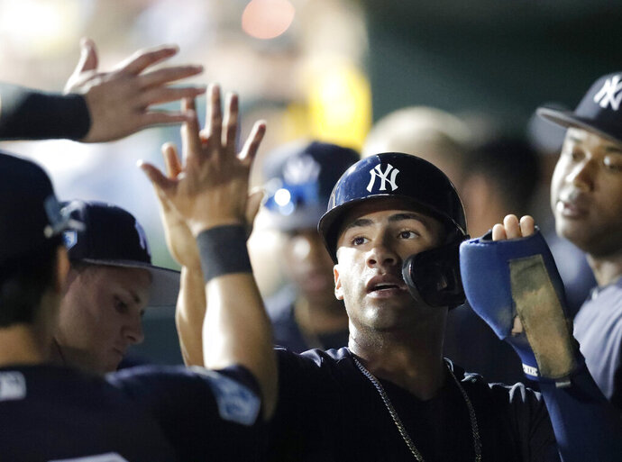 New York Yankees' Gleyber Torres (25) celebrates in the dugout after scoring on a Greg Bird single in the fourth inning of a spring training baseball game against the Baltimore Orioles Saturday, March 9, 2019, in Sarasota, Fla. (AP Photo/John Bazemore)