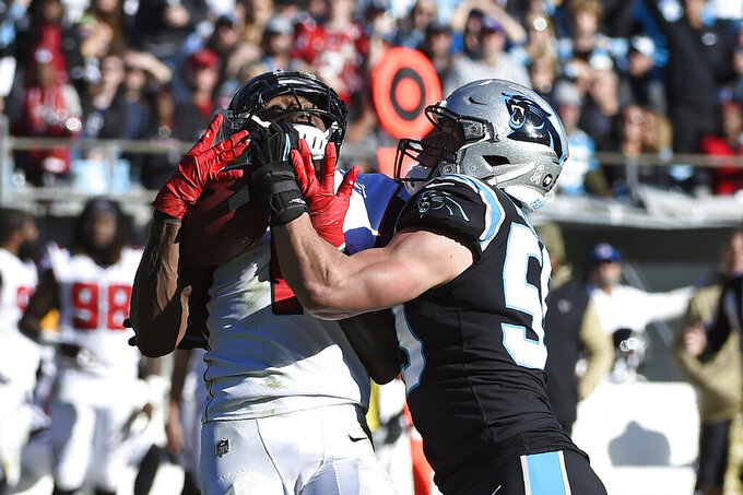 Atlanta Falcons wide receiver Julio Jones (11) catches a pass while Carolina Panthers middle linebacker Luke Kuechly (59) defgends during the first half of an NFL football game in Charlotte, N.C., Sunday, Nov. 17, 2019. (AP Photo/Mike McCarn)