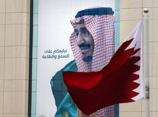 A Qatari flag flies in front of a banner showing Saudi King Salman with Arabic reads,