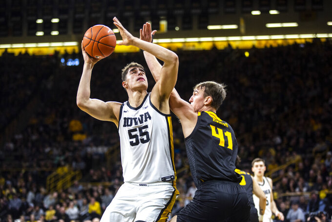 Iowa center Luka Garza (55) drives to the basket against Kennesaw State forward Drew Romich (41) during an NCAA college college basketball game, Sunday, Dec. 29, 2019, in Iowa City, Iowa. (Joseph Cress/Iowa City Press-Citizen via AP)