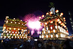 In this Tuesday, Dec. 3, 2019, photo,  lantern-covered floats stand as fireworks light up the sky during the Chichibu Night Festival in Chichibu, north of Tokyo, Japan. The Chichibu Night Festival, which has roots that go back more than 1,000 years, is one of three famous Japanese festivals to feature huge floats, which can top 7 meters (23 feet) and weigh up to 15 tons. (AP Photo/Toru Hanai)