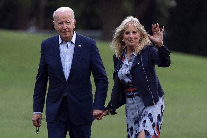 President Joe Biden and first lady Jill Biden walk on the South Lawn of the White House after stepping off Marine One, Sunday, July 18, 2021, in Washington. The Bidens are returning to Washington after spending the weekend at Camp David. (AP Photo/Patrick Semansky)