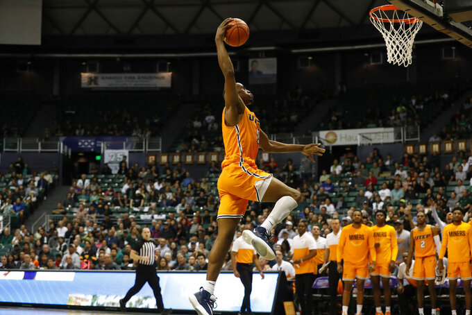 UTEP forward Bryson Williams (11) makes a slam dunk over Hawaii during the second half of an NCAA college basketball game Sunday, Dec. 22, 2019, in Honolulu. (AP Photo/Marco Garcia)
