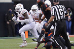 Texas's Joseph Ossai, left, carries a the ball after recovering an Oklahoma State fumble in the second half of an NCAA college football game in Stillwater, Okla., Saturday, Oct. 31, 2020. (AP Photo/Sue Ogrocki)
