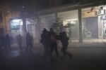 Riot police detains a man during minor clashes in Athens, Friday, Dec. 6, 2019. Thousands of protesters in Greece have joined marches in the nation's capital and other cities to mark the anniversary of the fatal police shooting of a teenager that sparked extensive rioting 11 years ago. (AP Photo/Yorgos Karahalis)