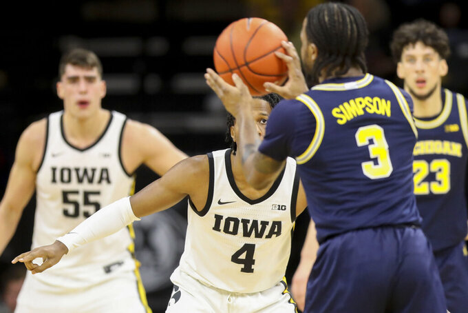 Iowa guard Bakari Evelyn (4) keeps an eye on the ball as Michigan Wolverines guard Zavier Simpson (3) looks to pass it during the first half of an NCAA college basketball game Friday, Jan. 17, 2020, in Iowa City, Iowa. (Rebecca F. Miller/The Gazette via AP)