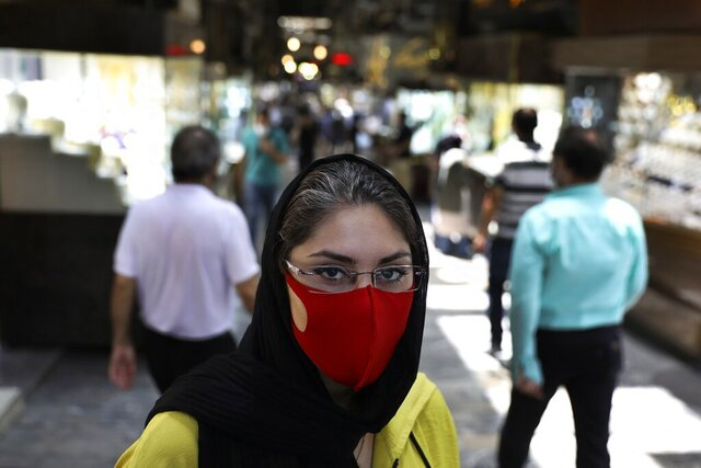 Reyhane Rajaei wearing a protective face mask to help prevent the spread of the coronavirus speaks with The Associated Press at a gold market of Tehran's Grand Bazaar, Iran, Wednesday, July 22, 2020.