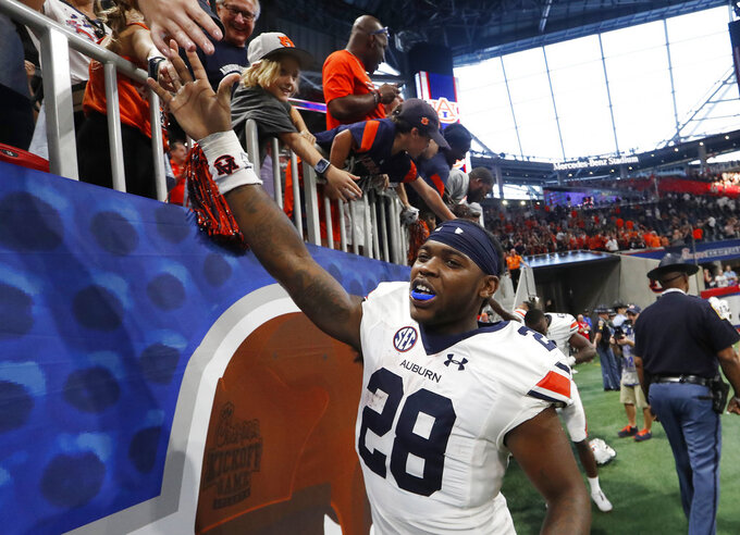Auburn running back JaTarvious Whitlow (28) celebrates with fans after Auburn defeated Washington 21-16 in an NCAA college football game Saturday, Sept. 1, 2018, in Atlanta. (AP Photo/John Bazemore)