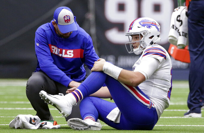 FILE - In this Oct. 14, 2018, file photo, Buffalo Bills quarterback Josh Allen (17) is check on after he was injured during the second half of an NFL football game against the Houston Texans in Houston. In making his NFL playoff debut against the Texans this weekend, second-year Buffalo Bills quarterback Josh Allen gets an opportunity to show how far he's come since his last trip to Houston 14 months ago. (AP Photo/Michael Wyke, File)