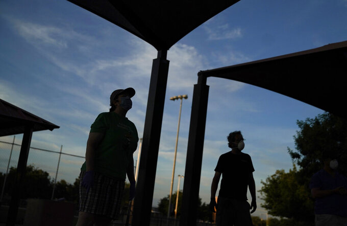 In this Wednesday, May 6, 2020, photo Ginger Bruner, left, plays bocce ball will friends at a park in Las Vegas. Bruner is a musician and hasn't worked since the coronavirus shutdown. (AP Photo/John Locher)