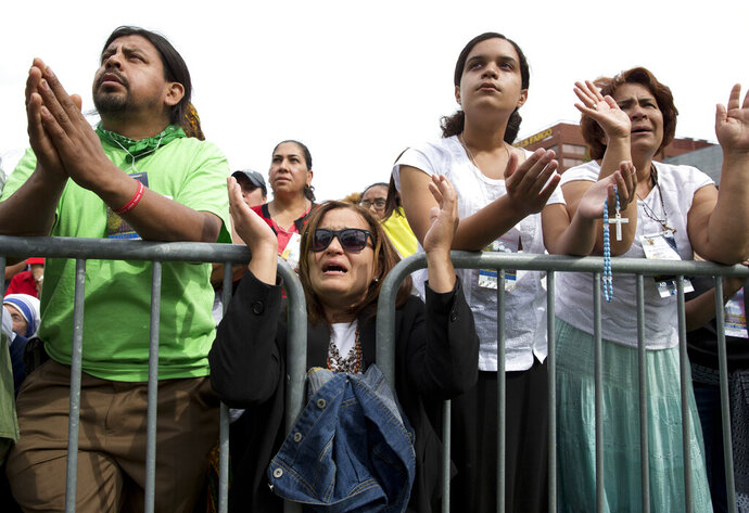 FILE - In this Saturday, Sept. 26, 2015 file photo, worshippers pray behind a barricade at Independence Mall in Philadelphia, as a Mass with Pope Francis at the Cathedral Basilica of Sts. Peter and Paul is projected on a large screen. In 2018-19, 47% of Latinos identified as Catholic, down from 57% a decade earlier. (AP Photo/Carolyn Kaster)