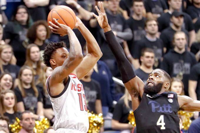 North Carolina State's C.J. Bryce, left, shoots as Pittsburgh's Jared Wilson-Frame (4) defends during the second half of an NCAA college basketball game, Saturday, Feb. 9, 2019, in Pittsburgh. North Carolina State won 79-76. (AP Photo/Keith Srakocic)