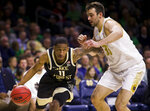 Wake Forest's Torry Johnson (11) drives in next to Notre Dame's John Mooney (33) during the first half of an NCAA college basketball game Wednesday, Jan. 29, 2020, in South Bend, Ind. (AP Photo/Robert Franklin)