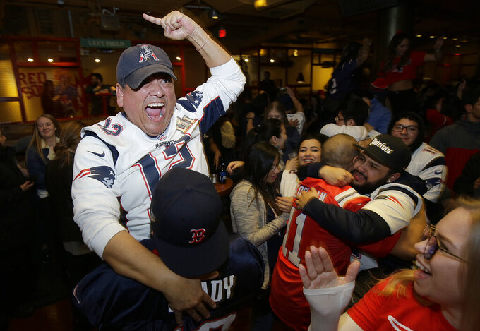 New England Patriots fan Victor Polanco, top, celebrates with others after the Patriots defeated the Los Angeles Rams in the NFL Super Bowl 53 football game in Atlanta at a bar in Boston on Sunday, Feb. 3, 2019. (AP Photo/Steven Senne)