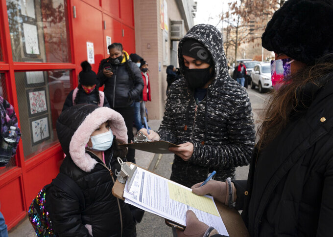 FILE - In this Dec. 7, 2020, file photo, a parent, center, completes a form granting permission for random COVID-19 testing for students as he arrives with his daughter, left, at P.S. 134 Henrietta Szold Elementary School, in New York. Children are having their noses swabbed or saliva sampled at school to test for the coronavirus in cities such as Baltimore, New York and Chicago. As more children return to school buildings this spring, widely varying approaches have emerged on how and whether to test students and staff members for the virus.(AP Photo/Mark Lennihan, File)